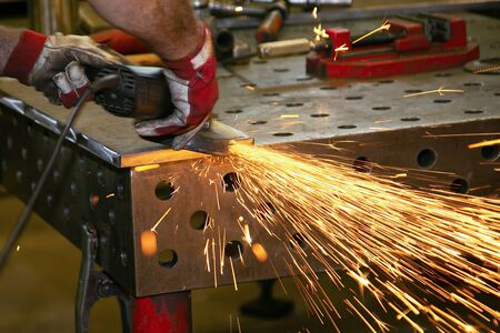 Manual processing of an industrial part with a angle grinder Фото со стока