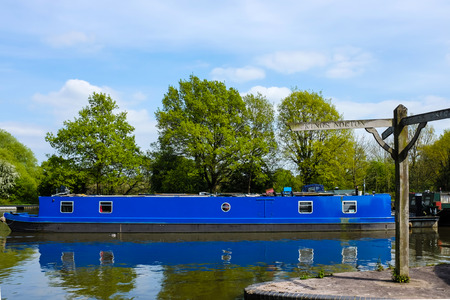 Blue British canal boat parked in a dock at Lapworth, a Warwickshire village.