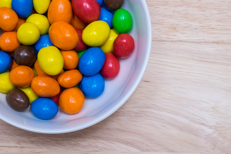 suger: Colorful suger coated chocolate in a white bowl