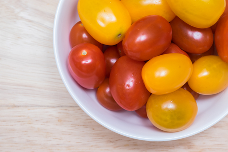 Red and yellow cherry tomatoes in a bowl. Stock Photo