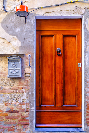 Beautiful front door with unique lamp and letter box in the town of Peccioli. Stock Photo