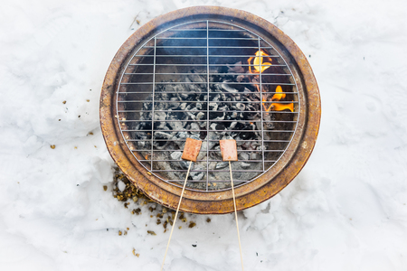 Barbeque snacks using a fire bowl in cold winter snow. Banco de Imagens