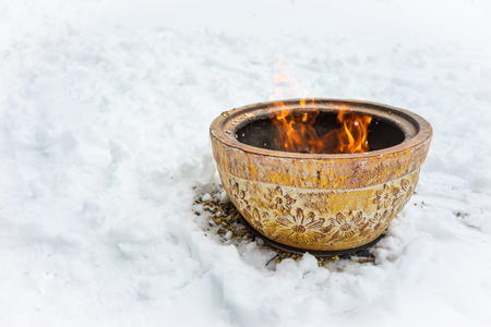 Fire bowl heating in a cold snowy winter. Stock Photo