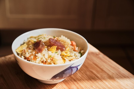 A bowl of Chinese fried rice with pork sausages and chopped vegetables. Stok Fotoğraf