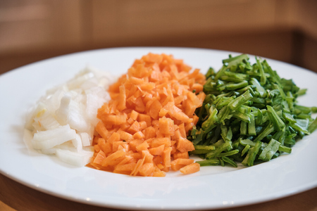 A plate of chopped onions, carrots and beans on a table.