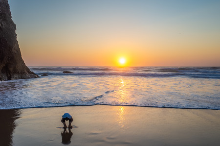 A little boy is playing with the sand at Praia da Adraga during sunset. Stok Fotoğraf