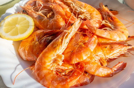 A plate of fried fresh king prawns with a slice of lemon.