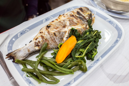 A plate of grilled fish with vegetable and carrot.