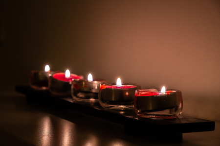 A roll of small red candles as light source.