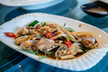 A plate of taiwanese style stir fried clams in a restaurant.