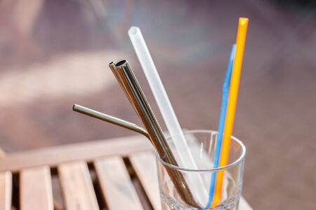 A collection of metal and plastic straws in a glass.
