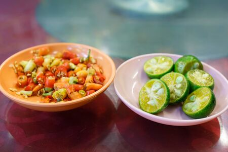A plate of chopped chilli and a plate of cut limes. Stockfoto