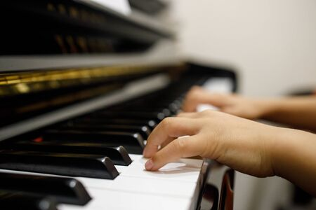 Two little childrens hand playing the piano.