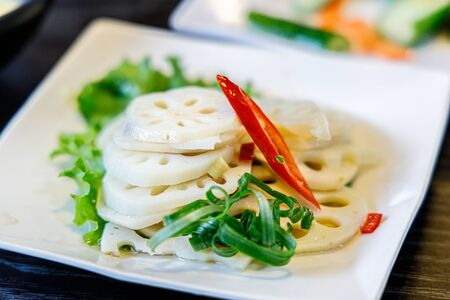 Sliced lotus root with spring onion and chilli on a plate Stockfoto