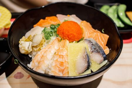 Mixed sashimi with sushi rice in a black bowl Stockfoto