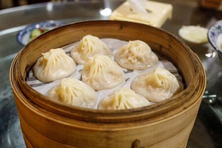 A tray of chinese dumplings with soup inside them
