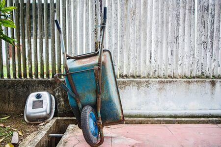 An old green wheelbarrow lying in a garden Stockfoto
