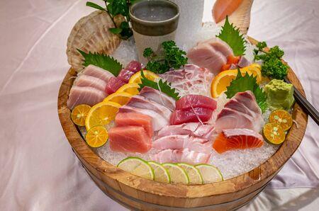 Assortment of fresh delicious Sashimi on large bucket with ice
