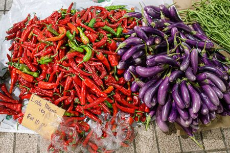Chilli and aubergine on the floor of local market. The words say 10 Riggit per kilogram Red Chilli.