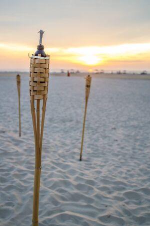 A few outdoor candles seen in a sandy beach at dusk