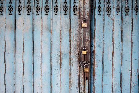 View of an old metal folding shop door with locks.