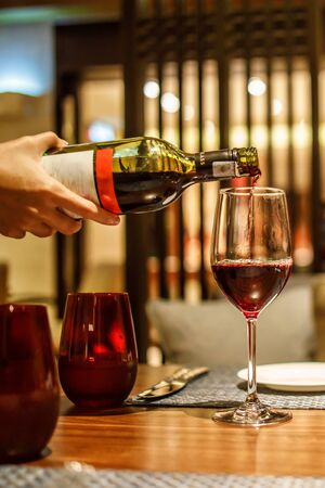 Waiter Pouring Red Wine into a Wine Grass Stockfoto