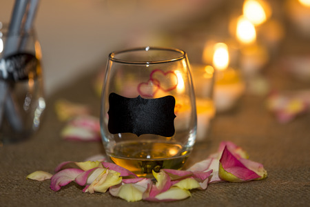 Burning candles at a wedding ceremony with a blank tag and hand drawn red hearts on a glass container with copy space for your message by romantic candlelight