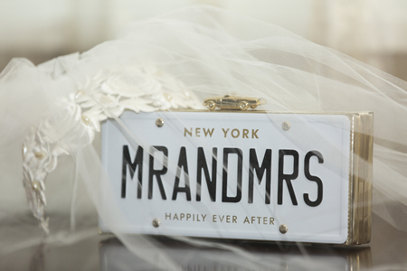 surmounted: Bridal veil with Mr and Mrs placard surmounted with a gold model car with the words Happily Ever After below celebrating the marriage of two newlyweds Stock Photo