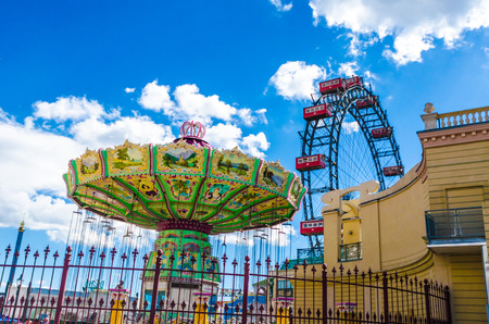 big top: Fairground in Vienna with a ferris wheel and colourful spinning big top offering rides to passengers during a festival or carnival behind an ornate railing against a cloudy blue summer sky