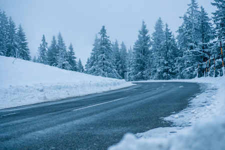lena: Bend in an icy snow covered road through evergreen coniferous forests in winter on a bleak cold day with grey sky viewed low angle