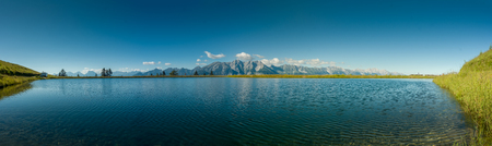 Scenic panorama of the Mutteralm hiking and skiing region of the Tyrol near Innsbruck with a distant mountain range behind a tranquil lake