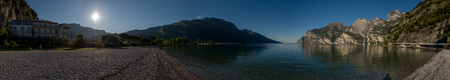stoney: Panorama of lake shore in mountains with sun in the sky and building near stoney beach Stock Photo