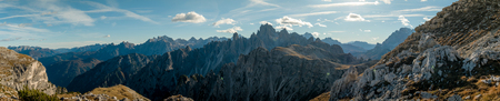 steep: Mountains panorama with rocky peaks and blue sky with contrails and clouds Stock Photo