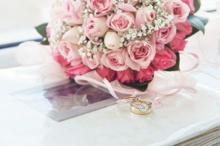 diamond ring, red and white gold ring and bouquet of roses on a wedding photo album Stock Photo - 18851520