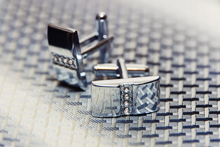 cuff: Pair of silver cuff links on the mans tie