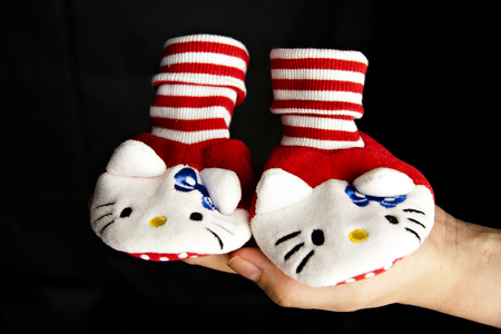 Babys red ahd white bootee on the hand on black background