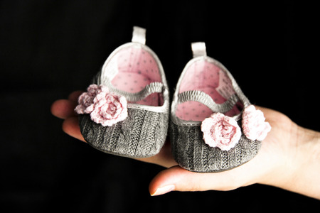Babys grey bootee with pink flowers on the hand on black background Stock Photo