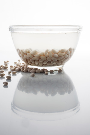 scattered: Soaked and scattered beans on white with reflection