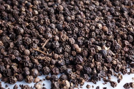 black pepper: Scattered black pepper on white