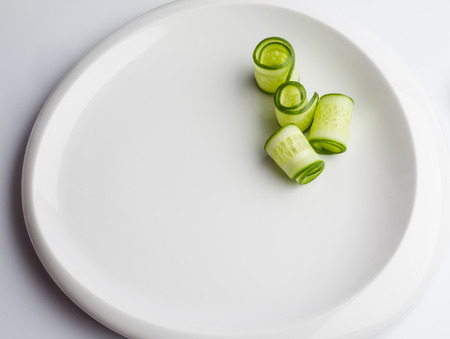 rolled: Rolled cucumber slices on white plate Stock Photo
