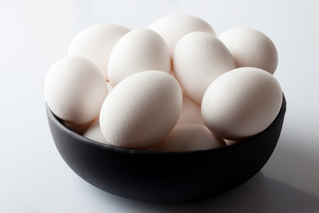 white eggs: White eggs in a black bowl on white background from high angle with shadow
