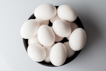 huevo blanco: Huevos blancos en un tazón negro sobre fondo blanco desde arriba Foto de archivo