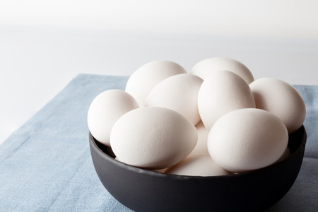White eggs in a black bowl on blue linen napkin on white background from side off centre composition