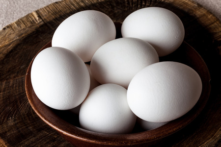 white eggs: White eggs in a brown clay cracked bowl on wooden old weathered cracked cutting board on rough beige rural map closeup from above Stock Photo