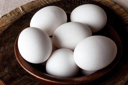 Witte eieren in een bruine klei gebarsten kom op houten oude verweerde gekraakt snijplank op ruwe beige landelijke kaart close-up van bovenaf