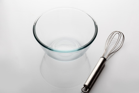 whisker: Glass transparent bowl with metal whisker aside on white background from high angle with reflection Stock Photo