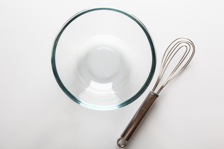 whisker: Glass transparent bowl with metal whisker aside on white background directly from above with reflection