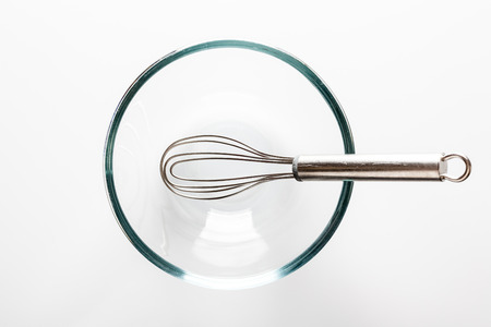 whisker: Glass transparent bowl with metal whisker inside on white background directly from above