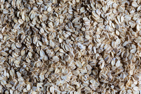 directly: Oatmeal rolled oats grains spread evenly on surface directly from above