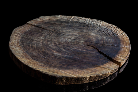Old rough wooden cutting board on black surface from high angle Banco de Imagens
